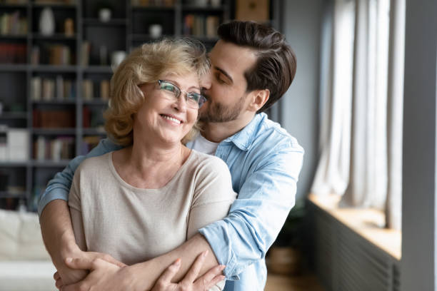 Loving adult son kissing and hugging happy mature mother stock photo