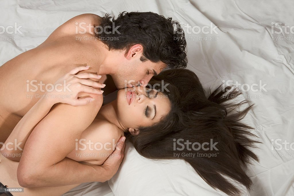 Loving affectionate nude heterosexual couple on bed in affection royalty-free stock photo