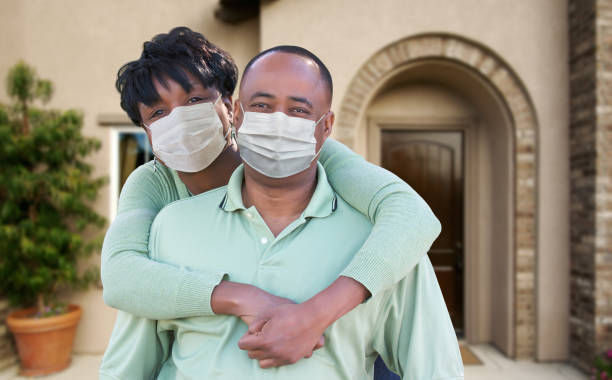 Loving African American Couple Hugging Wearing Medical Face Masks In Front of House stock photo