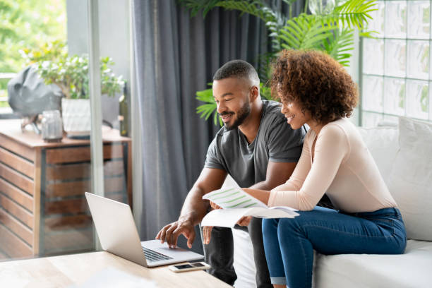Loving African American couple paying bills online at home stock photo