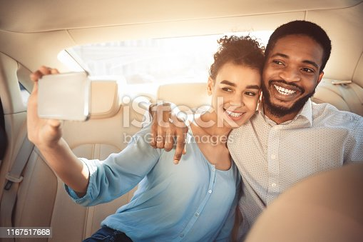 807410214istockphoto Loving african american couple taking selfie, driving in car 1167517668