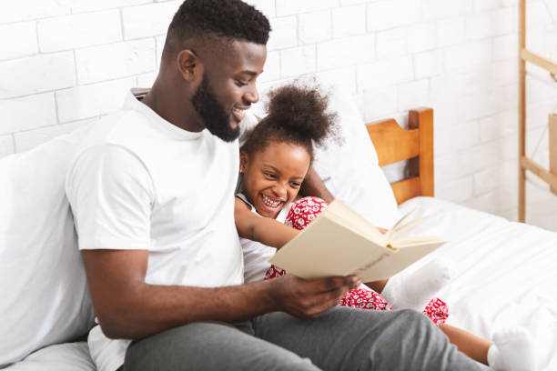 Loving african american dad reading fairy tales to his little daughter Story time. Loving african american dad reading fairy tales to his little daughter, sitting together on bed fairy tale stock pictures, royalty-free photos & images