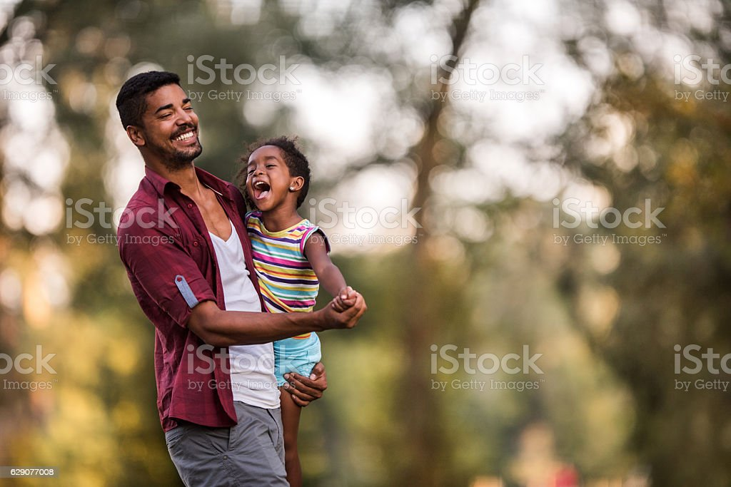 Loving African American father and daughter dancing in nature. stock photo