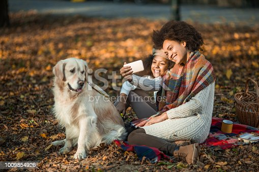 istock Loving African American mother and daughter having fun while taking a selfie with mobile phone. 1009854926