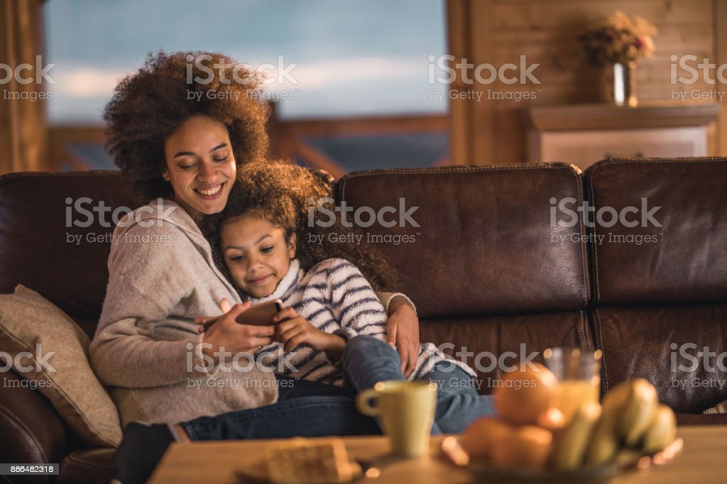 Loving African American mother and daughter watching cartoons on cell phone at home. stock photo