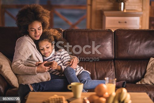 istock Loving African American mother and daughter watching cartoons on cell phone at home. 932650700