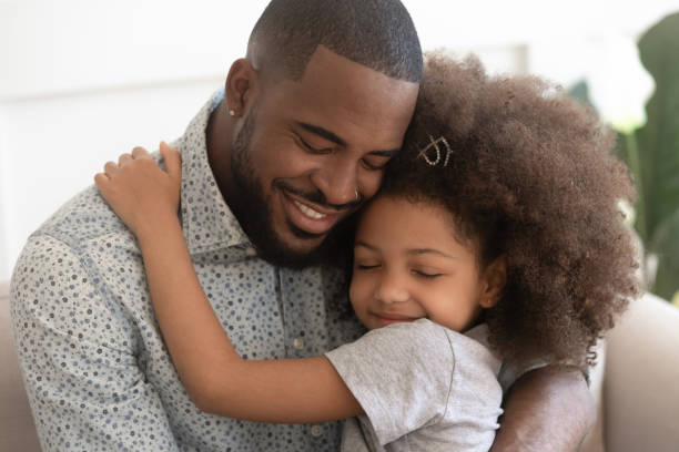 Loving african father hug cute child daughter with eyes closed Loving african american father hug cute little child daughter embrace single black dad with eyes closed, happy mixed race daddy and small kid princess wear crown enjoy moment of affection together genderblend stock pictures, royalty-free photos & images