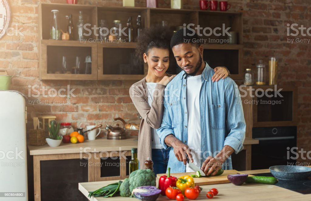 Loving african-american couple cooking in loft kitchen stock photo