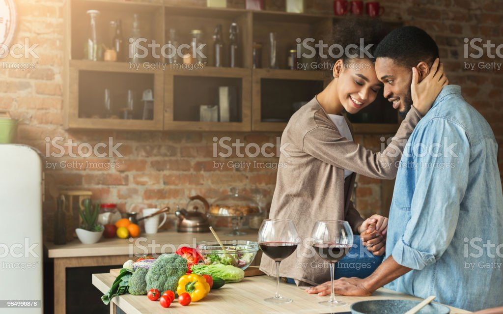 Loving african-american couple drinking wine in kitchen. stock photo