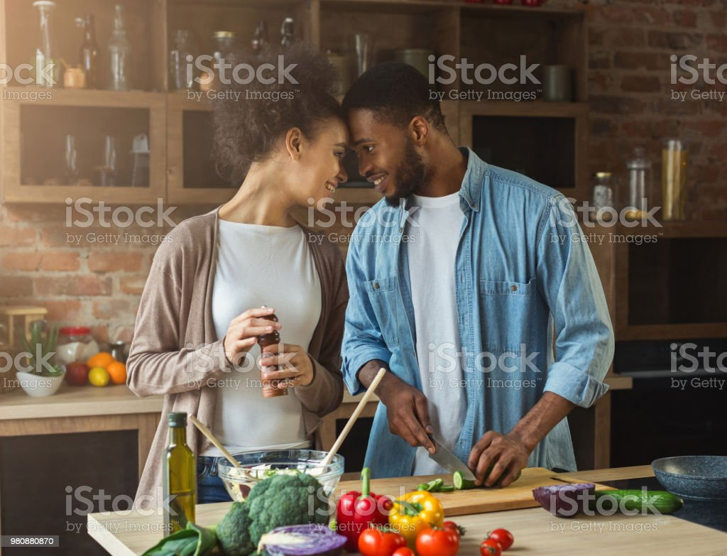 Loving african-american couple preparing dinner in kitchen stock photo