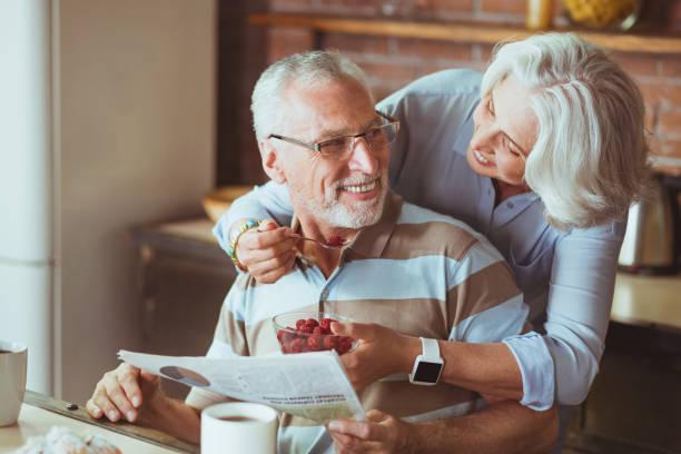 Loving aged couple enjoying their breakfast stock photo