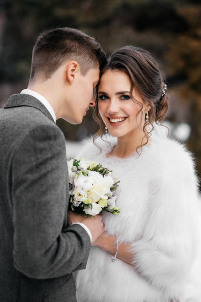 Loving and beautiful bride and groom stand in an embrace in the winter forest. Vertical frame stock photo