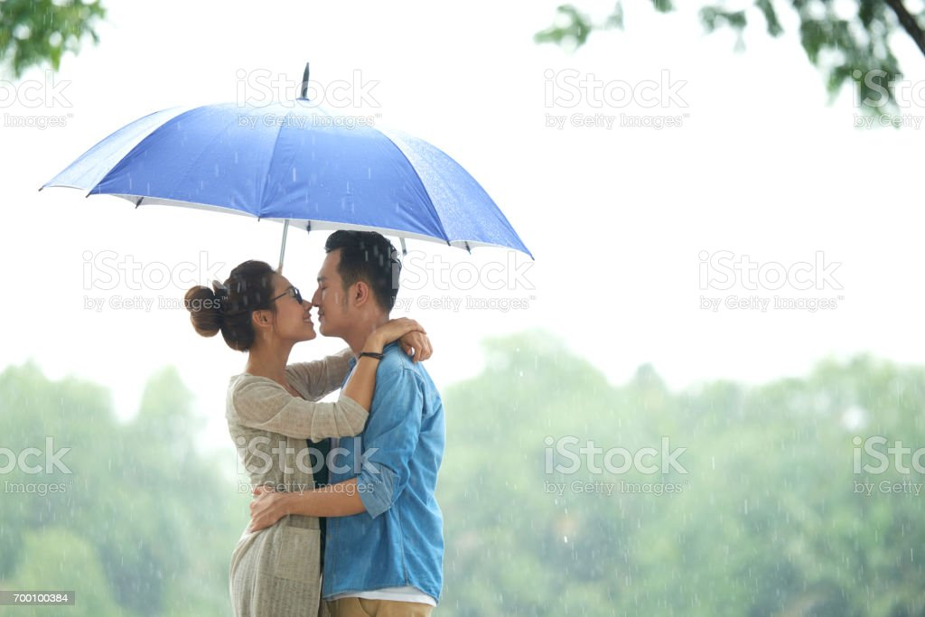 Loving Asian Couple in Rain under Umbrella stock photo