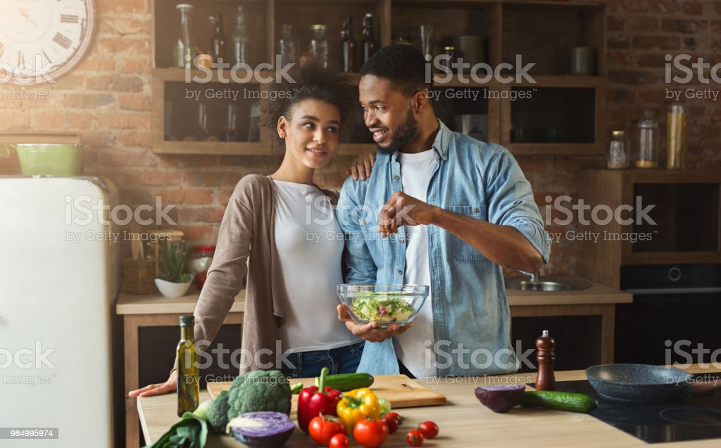Loving black couple cooking green salad in kitchen stock photo