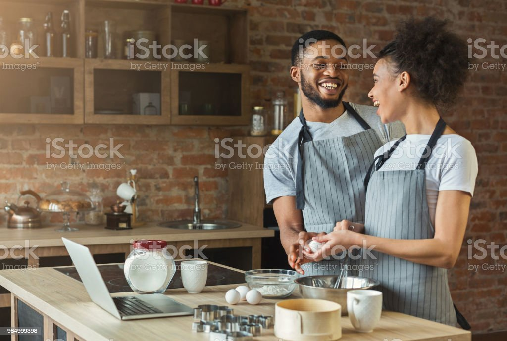 Loving black couple cooking pastry in loft kitchen stock photo