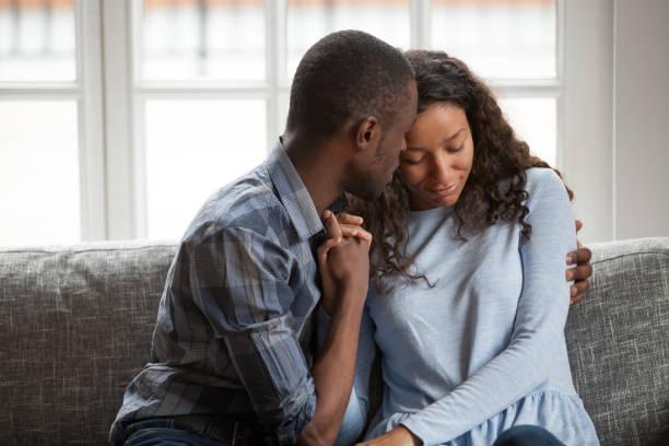 loving black couple hug on couch making peace after fight - seduzione foto e immagini stock