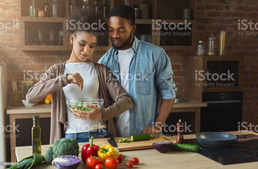 Loving black couple preparing dinner in kitchen stock photo