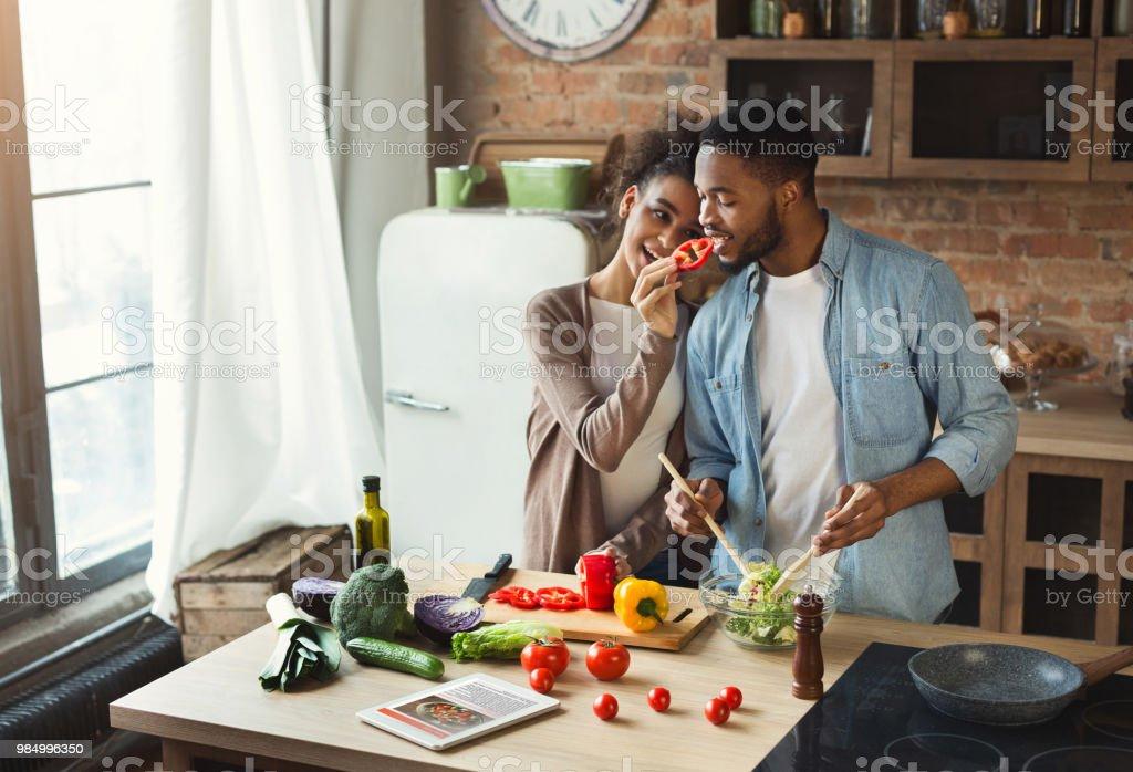Loving black couple preparing dinner stock photo