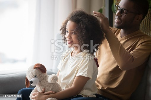 Loving young african American dad sit on couch with preschooler daughter brush curly hair, caring black father spend time with girl child take care making hairdo relaxing at home together