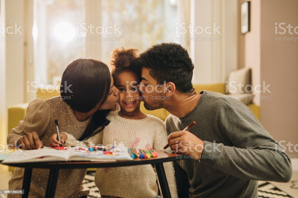 Loving black parents kissing their daughter during creative time at home. - Royalty-free Adult Stock Photo