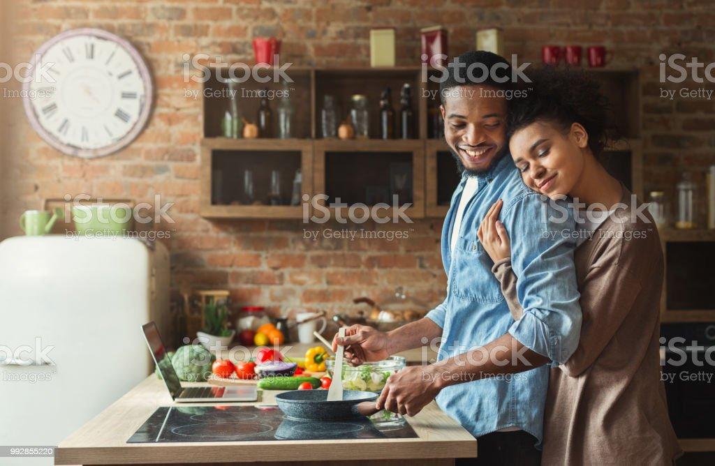 Loving black wife and husband preparing dinner in kitchen stock photo