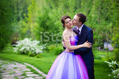 674214372istockphoto Loving bride and groom kissed in the green nature 174930067