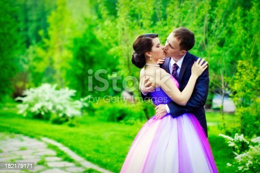 674214372istockphoto Loving bride and groom kissed in the green nature 182179171