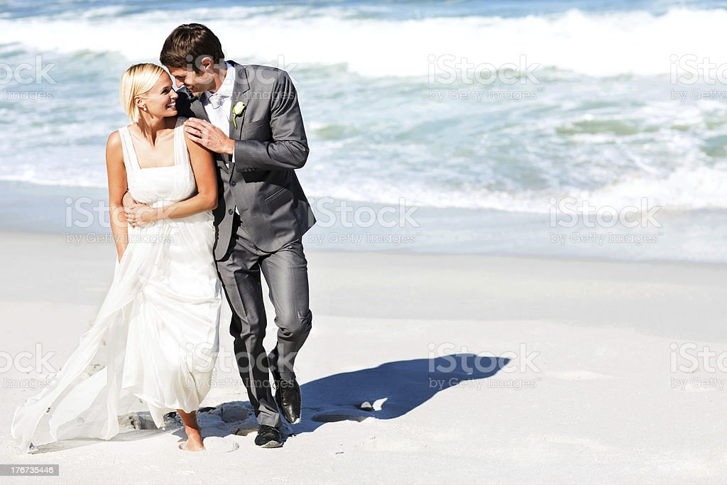 Loving Bride And Groom Walking On Beach stock photo