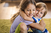 Happy kids embracing while showing affection towards each other at home.