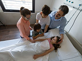 istock Loving brothers and parents visiting little girl lying down on hospital bed looking scared trying to cheer her up 1202155160