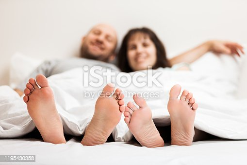 528422658 istock photo Loving caucasian couple in relationship lying and hugging on bed 1195430358