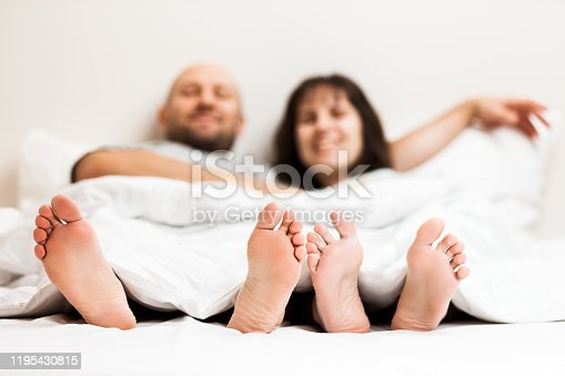 528422658 istock photo Loving caucasian couple in relationship lying and hugging on bed 1195430815