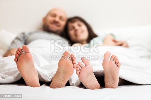 528422658 istock photo Loving caucasian couple in relationship lying and hugging on bed 1195430903