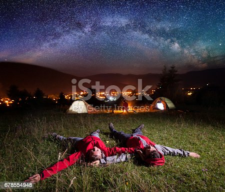 678554980istockphoto Loving couple admiring bright stars and lying on the grass 678554948