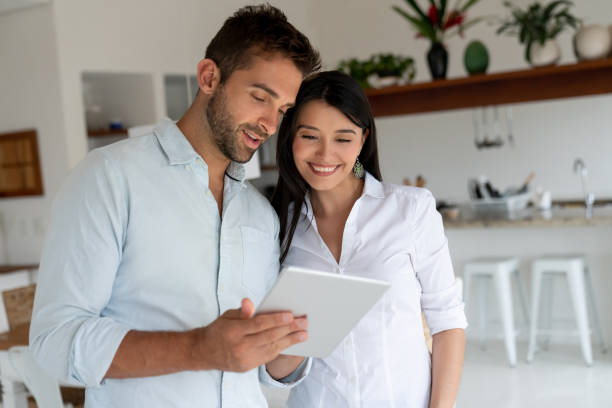 loving couple at home looking at social media on a digital tablet - being in a relationship with someone is going to require stock photos and pictures