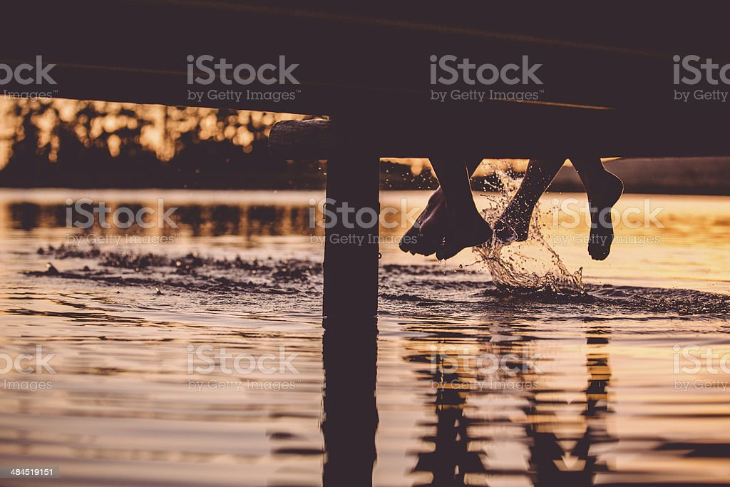 Loving couple at jetty (feet only) stock photo