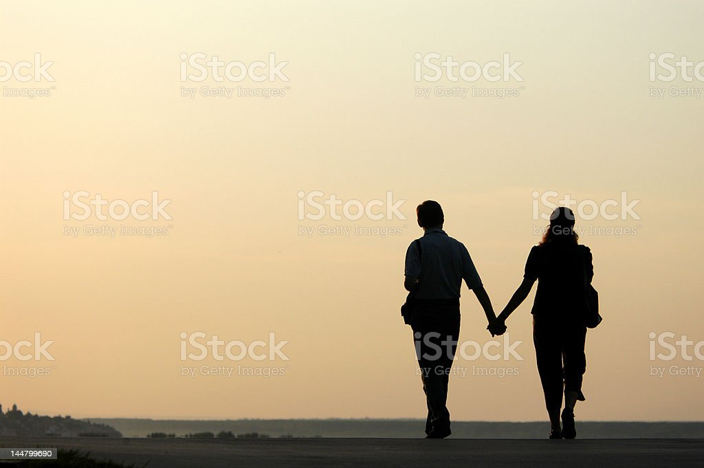 Loving Couple at Sunset Silhouetted loving couple walking at sunset Adult Stock Photo