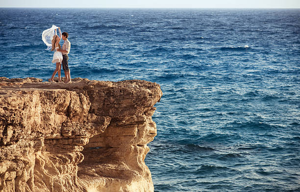 Loving couple at the end of sea cliff stock photo