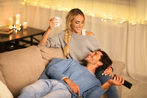 Loving couple drinking tea and enjoying winter holidays, talking and watching tv on sofa
