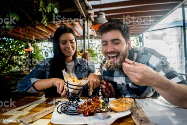 Loving couple eating together at a burgers restaurant picture id908850026?b=1&k=6&m=908850026&s=612x612&h=tmheypr01dexioqpv4xnpup9x8gqi994w0qp aaubug=