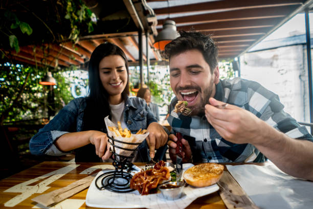 loving couple eating together at a burger's restaurant - dinner date stock photos and pictures