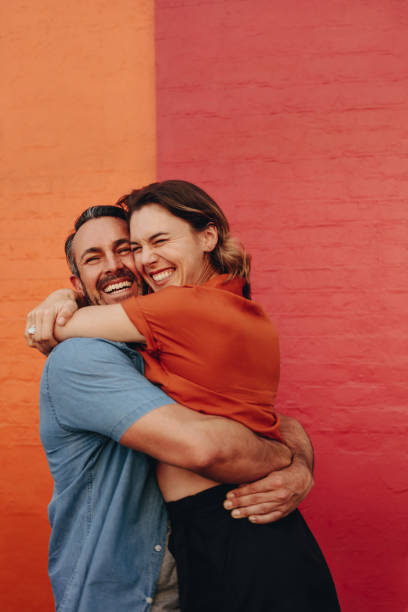 Loving couple embracing against colored wall stock photo