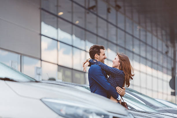 Loving couple embracing at airport car parking stock photo