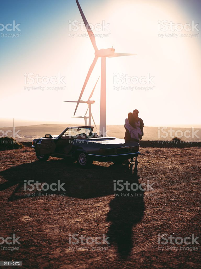 Young adult couple of lovers embracing outside near a convertible...