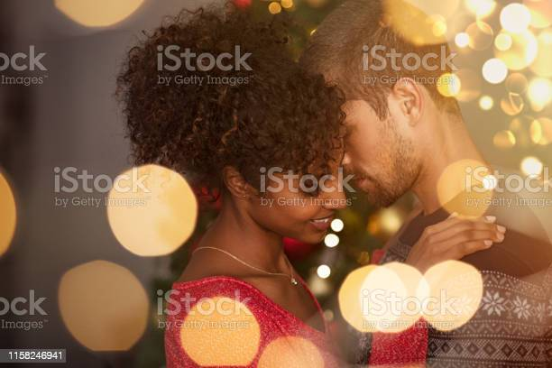 Loving couple embracing with warm lights Romantic couple in sweaters dancing before new year eve at home. Young lovely man and african woman hugging over christmas bokeh lights. Multiethnic couple dancing in love with golden lights bokeh in background. 20-29 Years Stock Photo