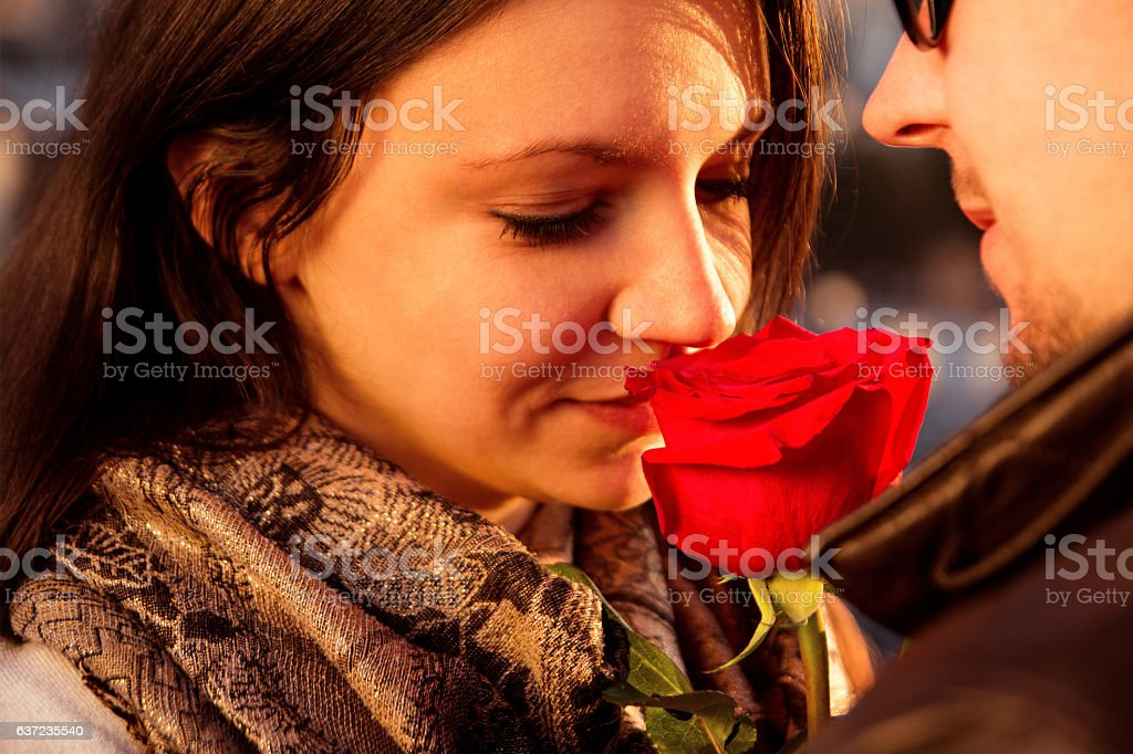 Loving couple enjoying the sun with red rose stock photo