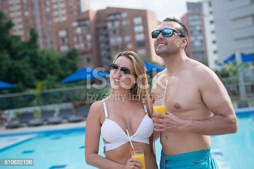 Loving couple enjoying their honeymoon and drinking cocktails by the pool on a summer day