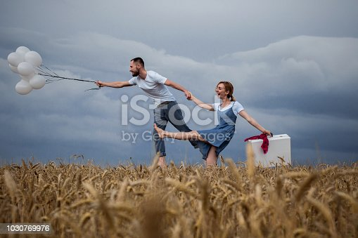 istock Loving Couple Flies to Heaven with Balloons. Relations. Love 1030769976