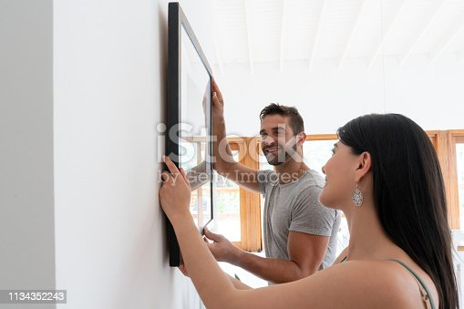 Portrait of a loving couple hanging a picture together at home – lifestyle concepts