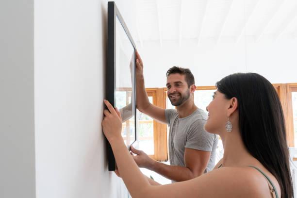 loving couple hanging a picture together at home - вешать стоковые фото и изображения
